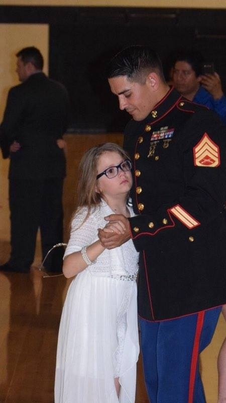 U.S. Marine Staff Sgt. William Liesenfelder and his daughter Scarlette dance to the last song at the AYSO daddy-daughter dance at Thornanpple Kellogg Schools.