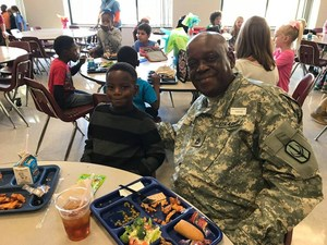 boy and his grandfather who is a veteran eating lunch