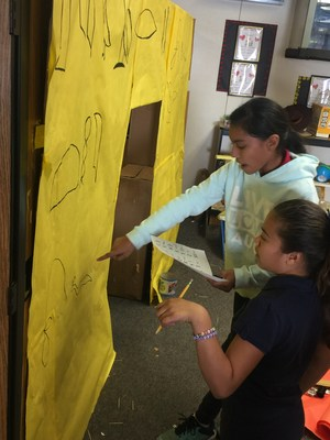 BPUSD_RUBE_1: Elwin Elementary School fifth-graders Sierra Villagran and Katelyn Haro paint a warning in an ancient language on the outside of their team's Rube Goldberg device as part of the Baldwin Park Unified 21st Century Challenge.