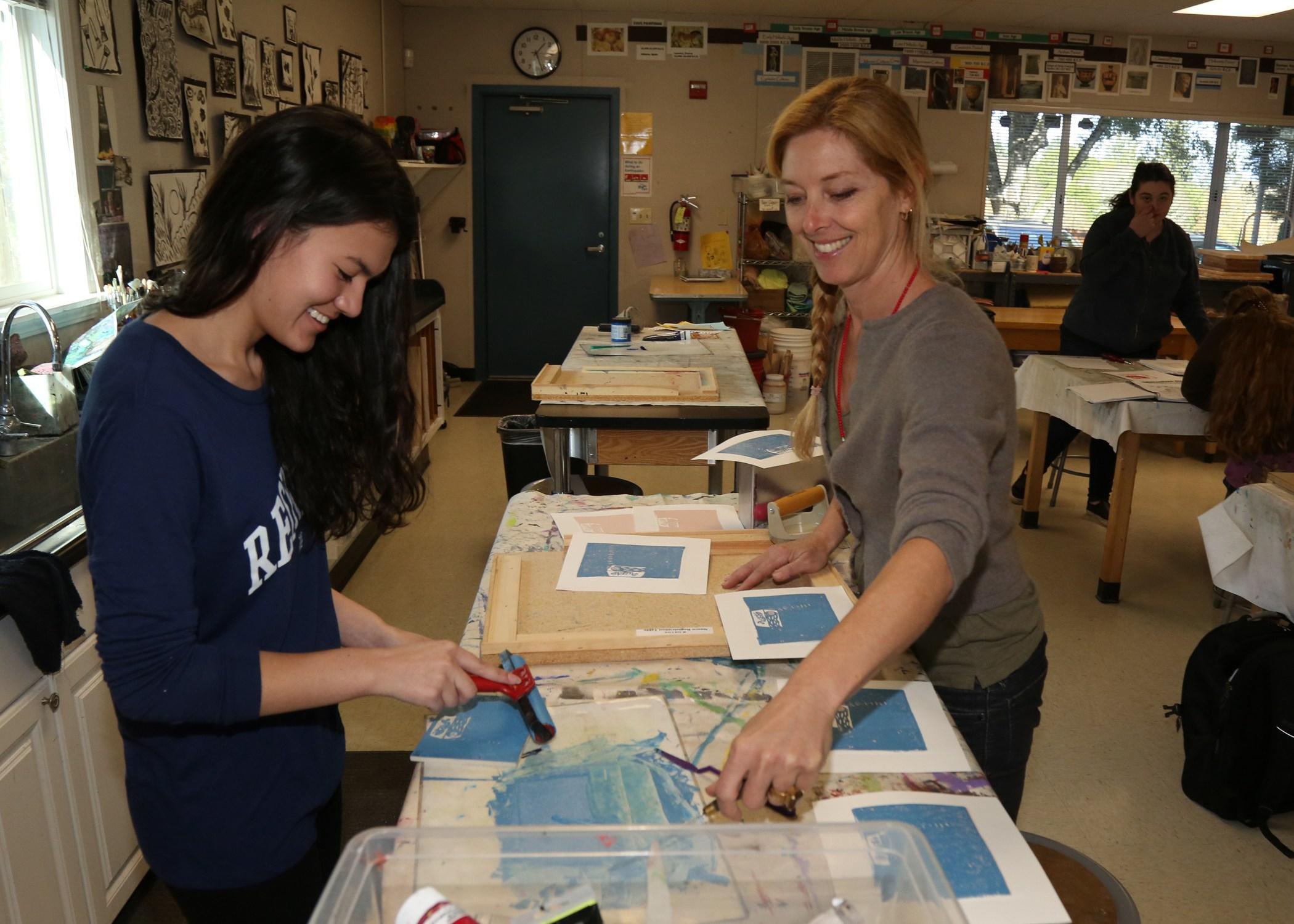 Art teacher with art student making a print