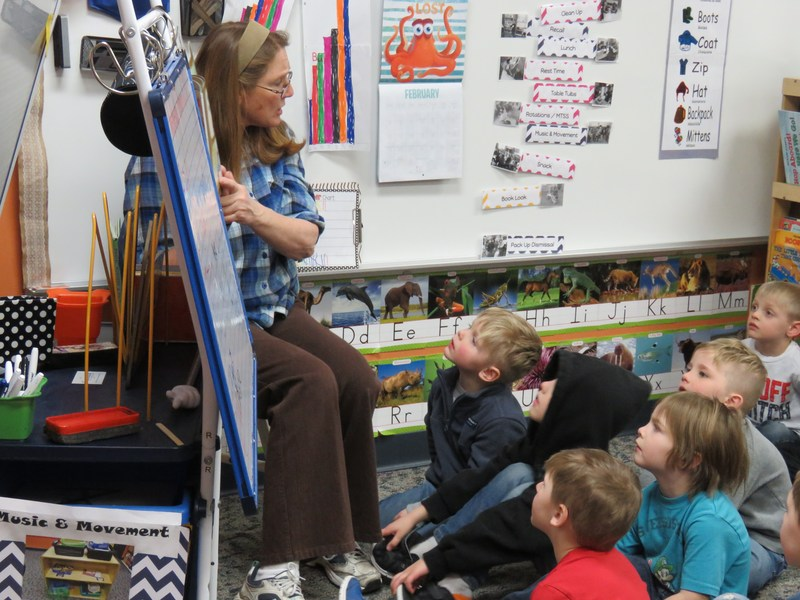 Preschool students at TK listen to a teacher read a story before lunch.