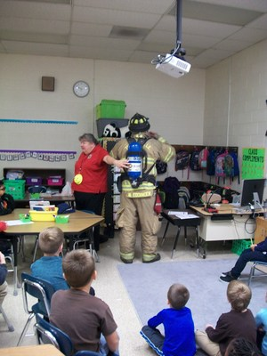 A fireman is dressed in fire gear as another firefighter describes how the air tank is used.