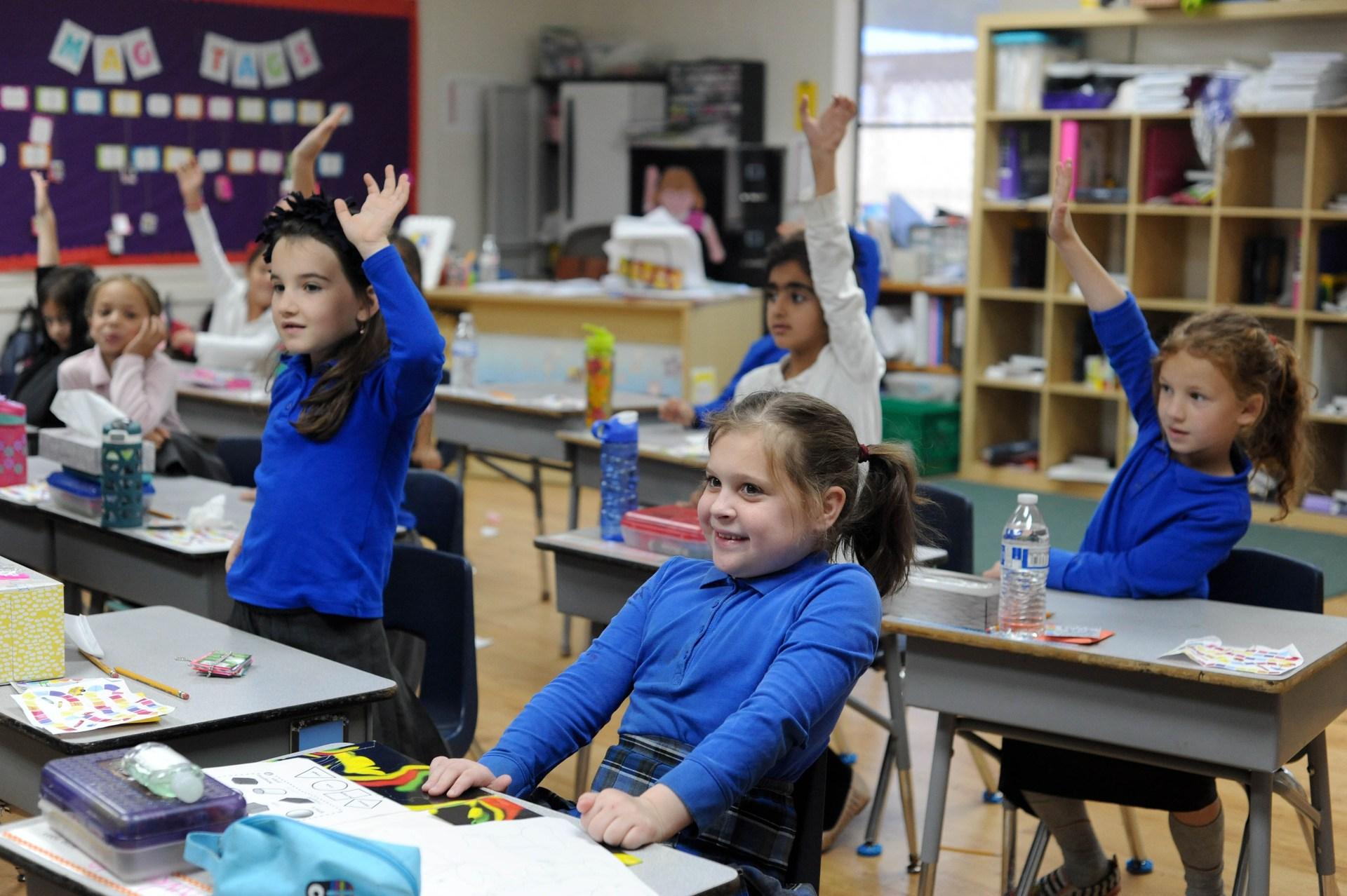 girls raising their hands in class