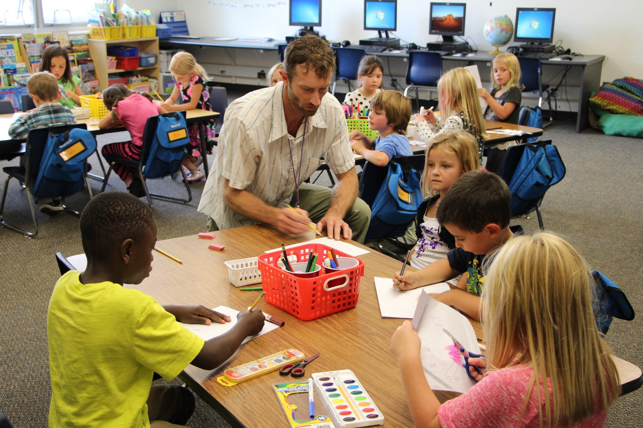 1st grade teacher Matt Ogburn works with students in his class.