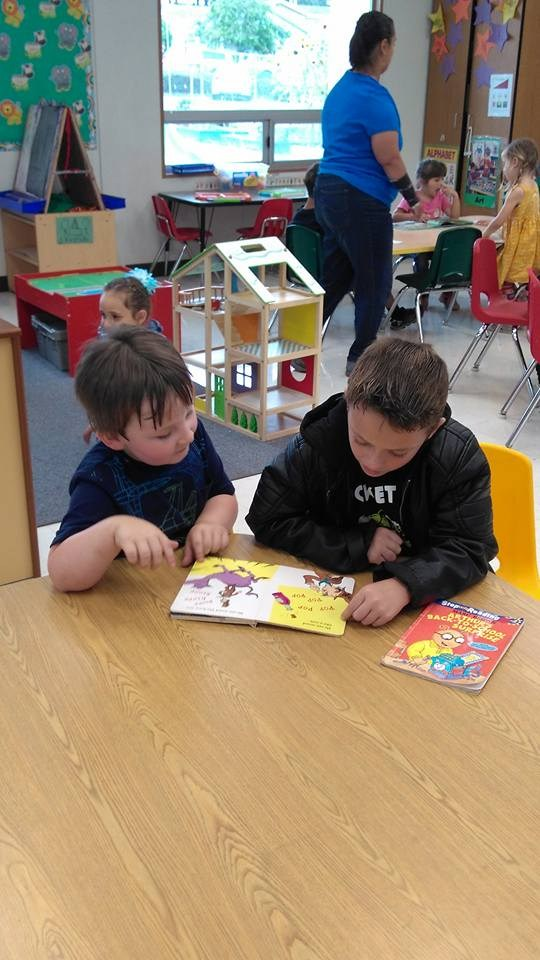 Older student reading to a younger student.