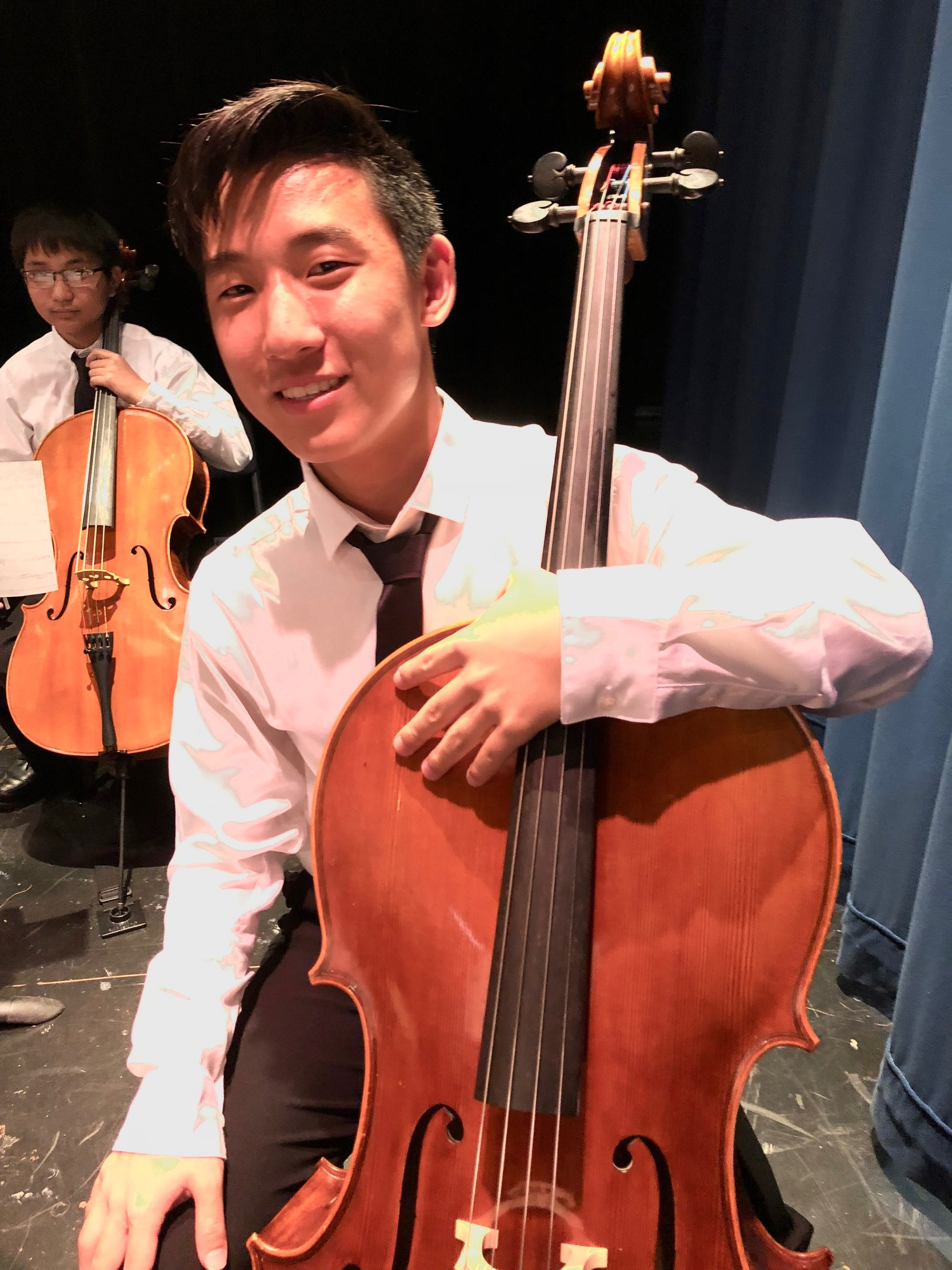 A boy posing with his cello.