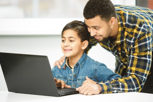 Father looking over son's shoulder at laptop screen with school CMS.