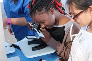 Casa Loma student looks into a microscope