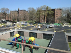 Early photo of a wide view of Frampton roof construction, playground equipment visible in play yard prior to most of the construction project.