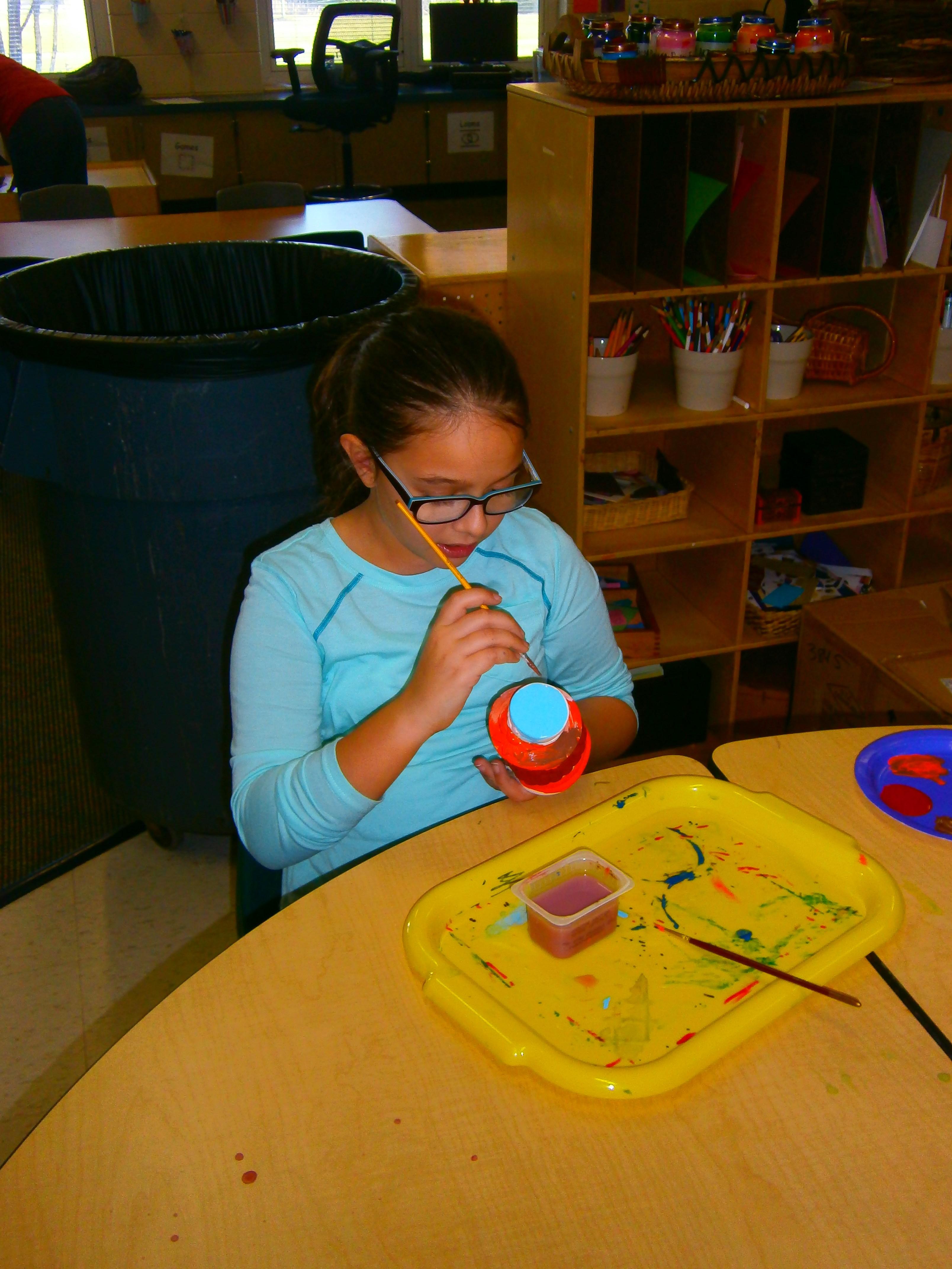 Girl painting a ceramic bowl.
