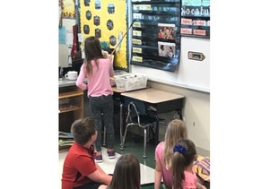 A first grade student leading her peers through a vocabulary review.