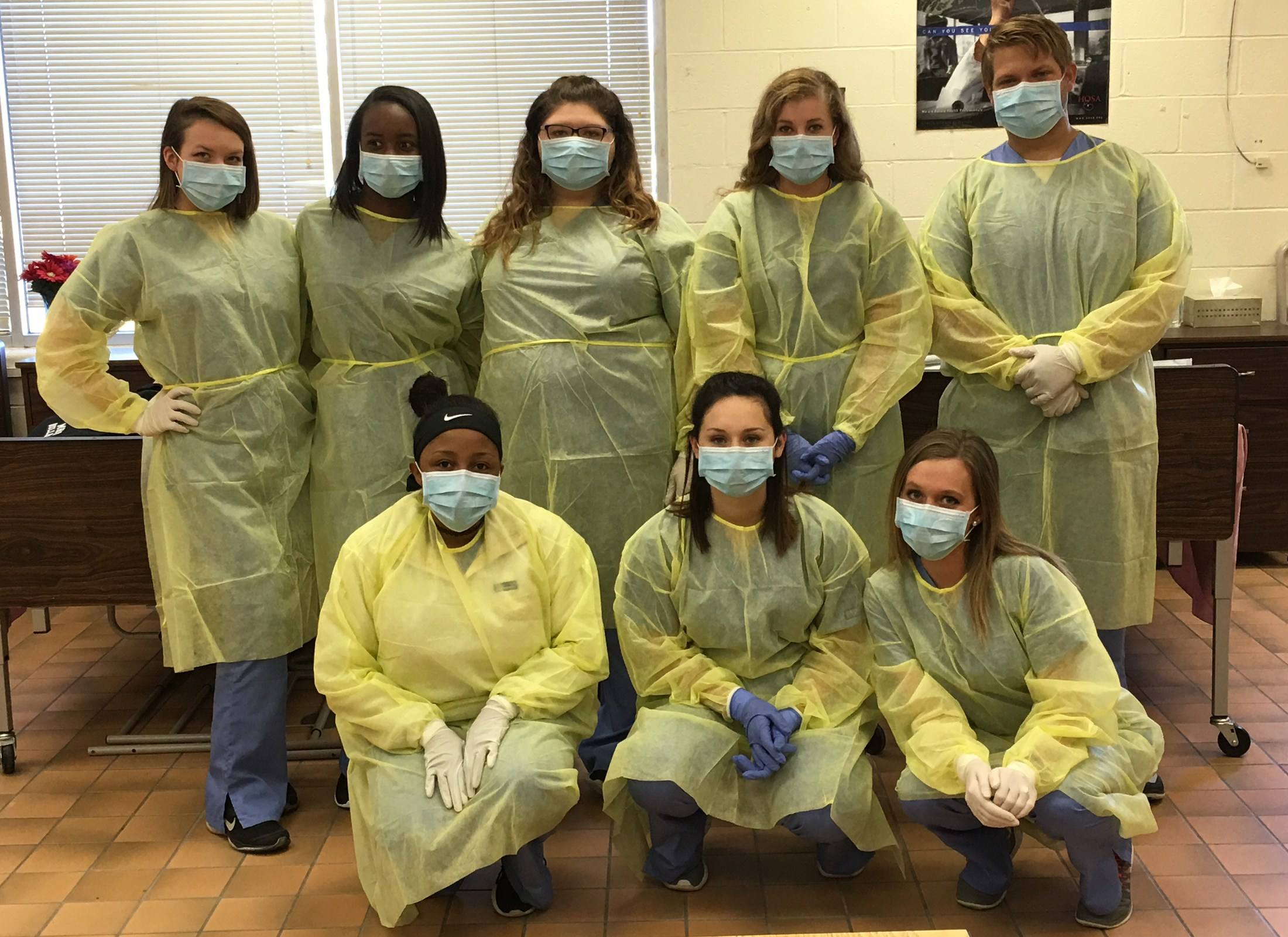 group photo in scrubs and gowns