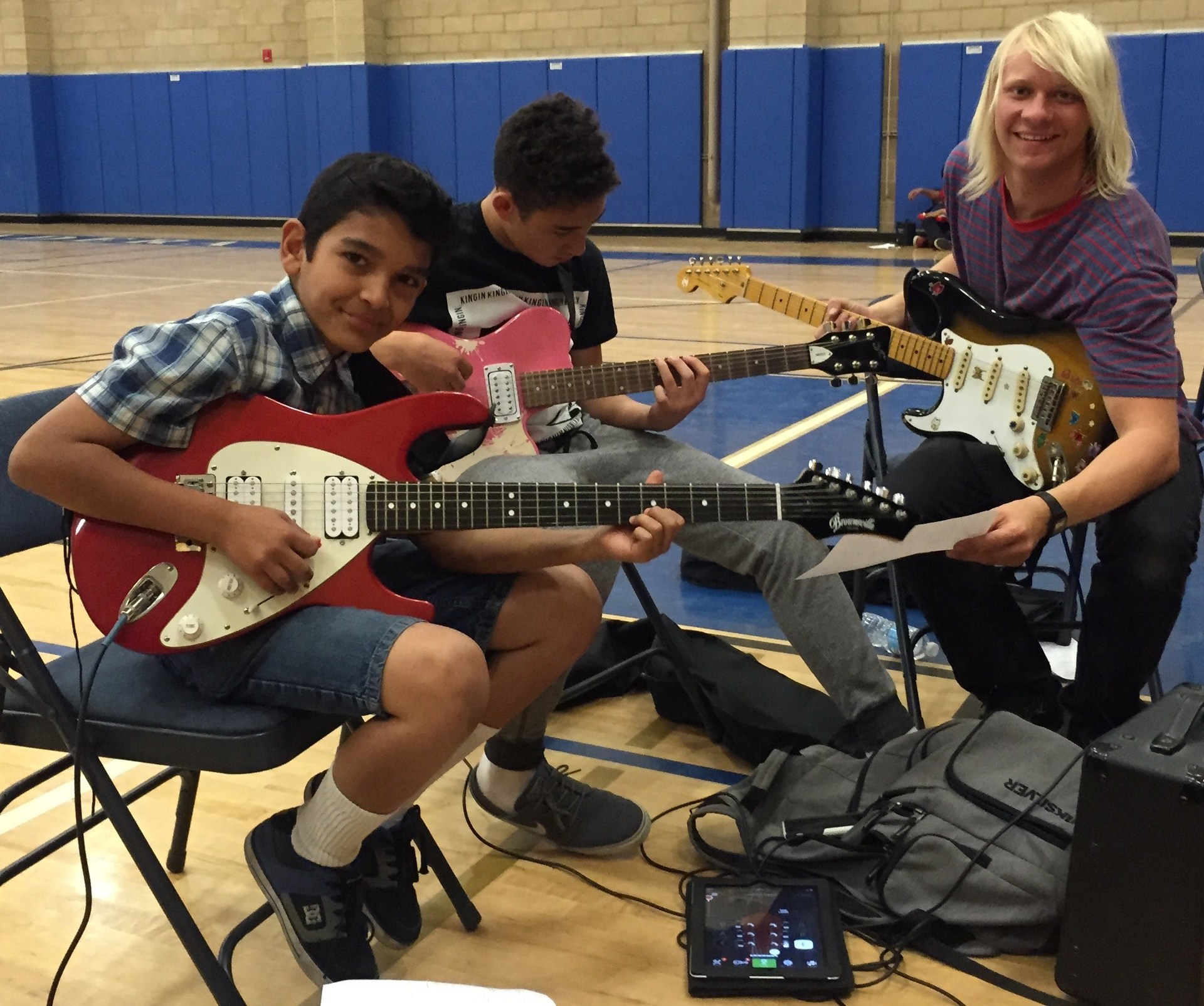 Students in an after school program playing the guitar.