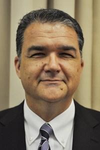 A headshot of a man smiling at the camera