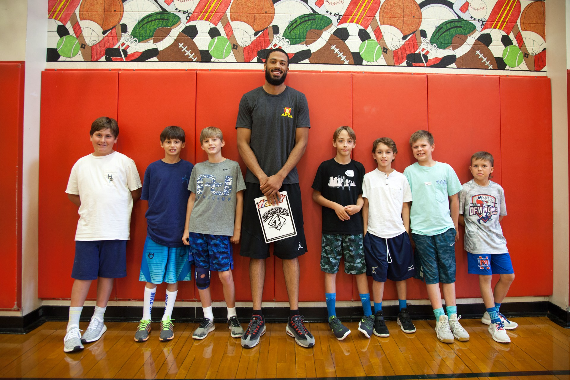 Elementary students smile for a photo with their PE coach in the gymnasium.
