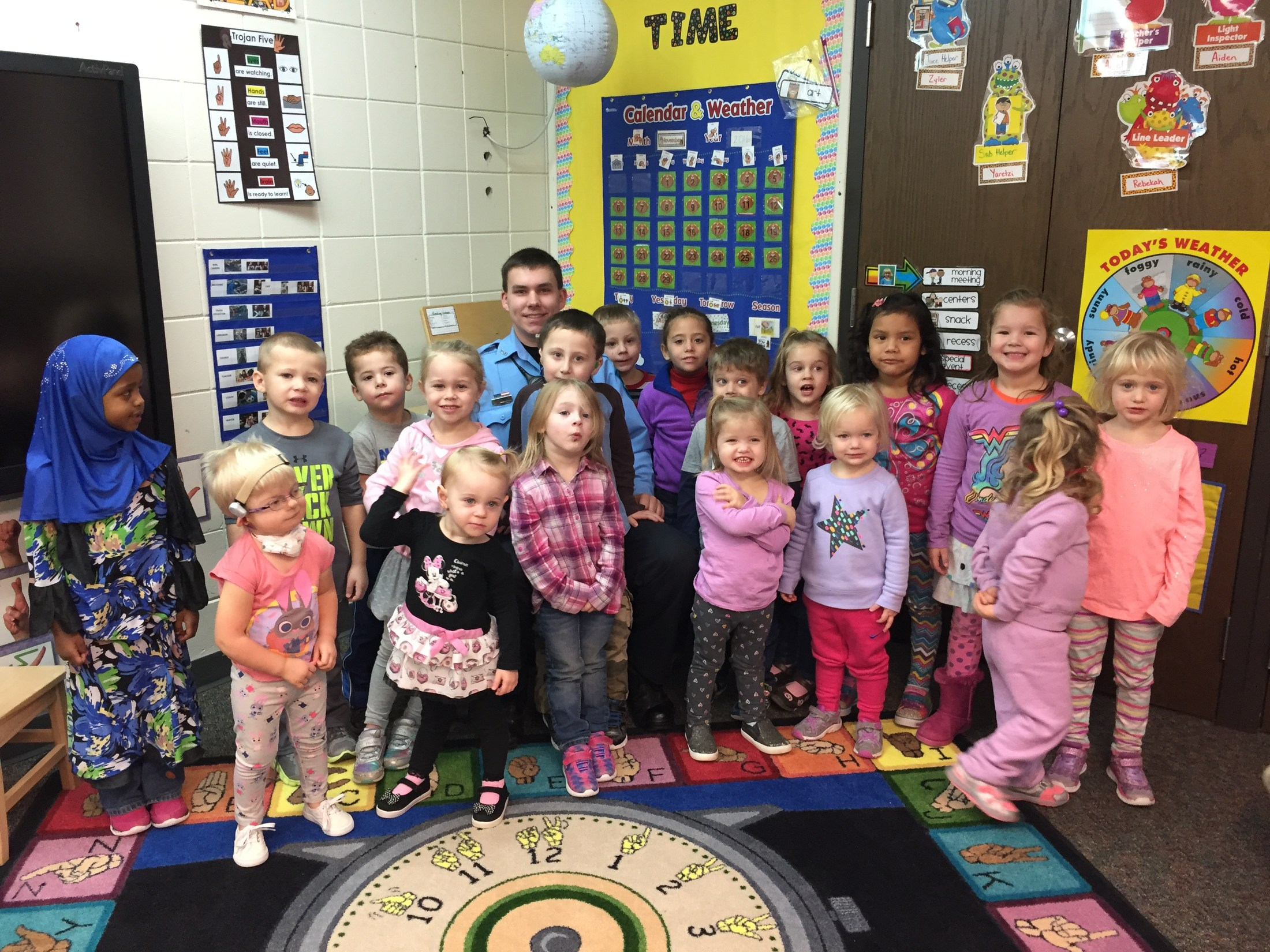 A group of 18 preschool students standing with a police officer in the classroom.