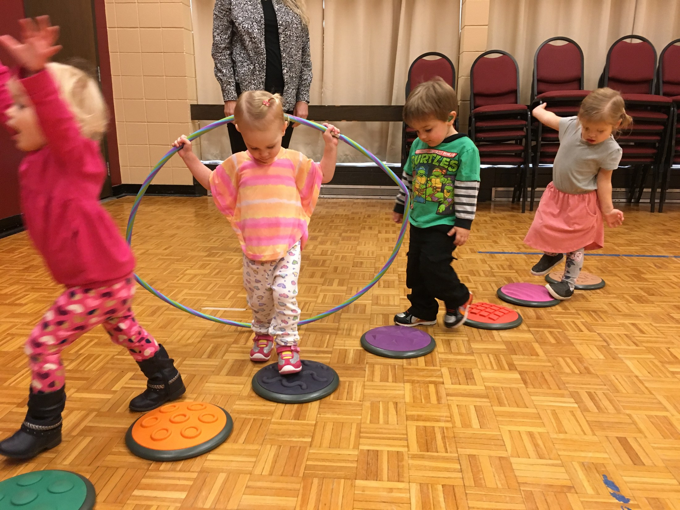Four students walking on circles in the gym in a line.