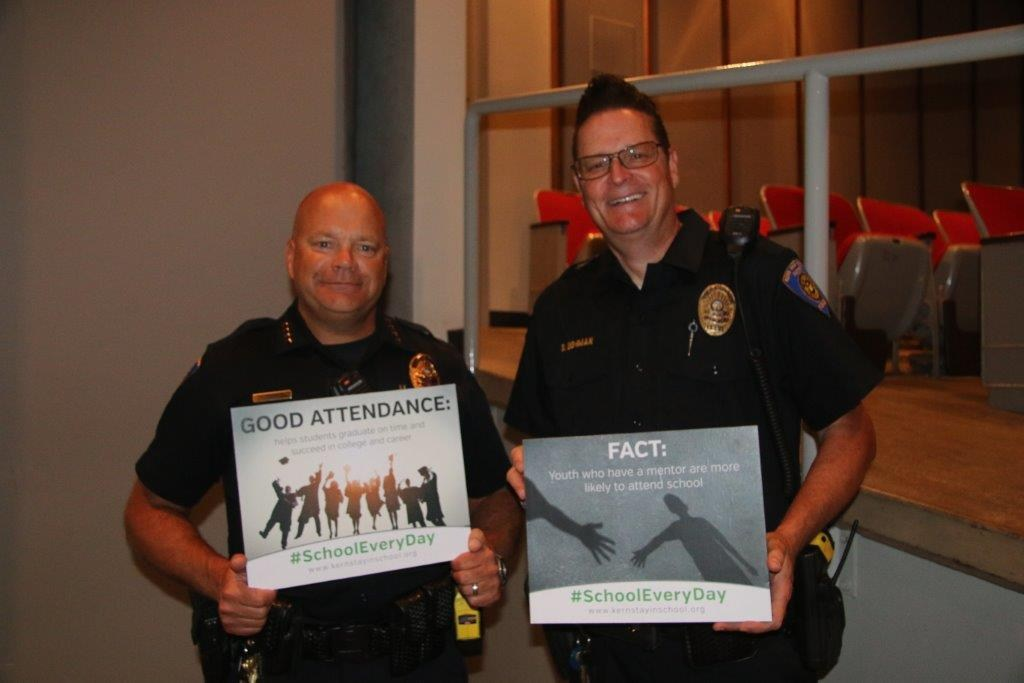 KHSD Police Chief holding a chronic absence sign