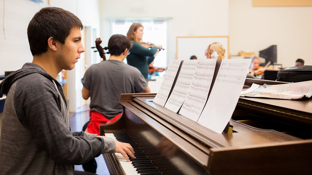 Student plays piano in foreground