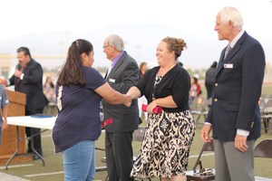 Governing Board Trustee Megan Haley shaking hands with a student.