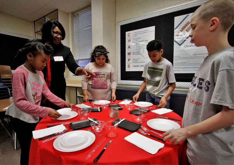 Etiquette class practices setting the table.