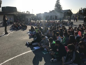 students sitting on blacktop listening to assembly