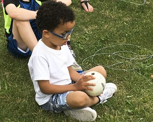 Young camper exploring the baseball.