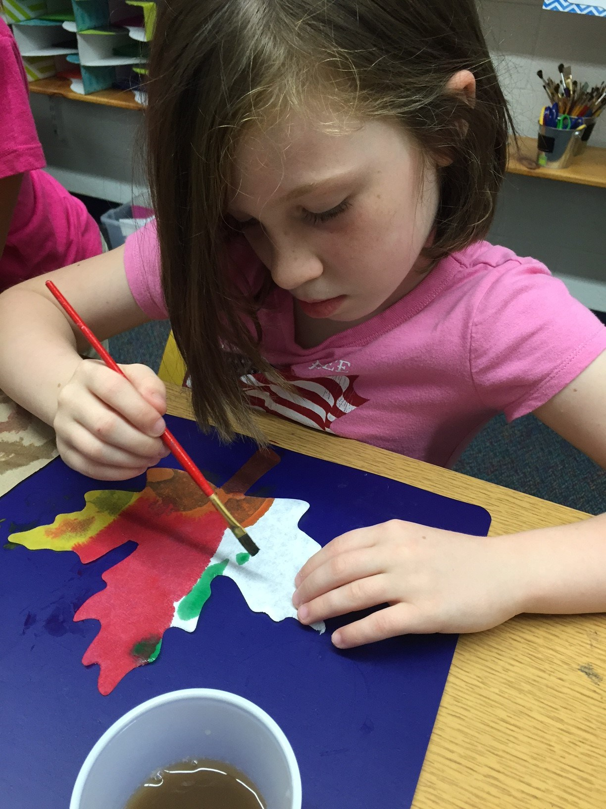 Girl painting a leaf.