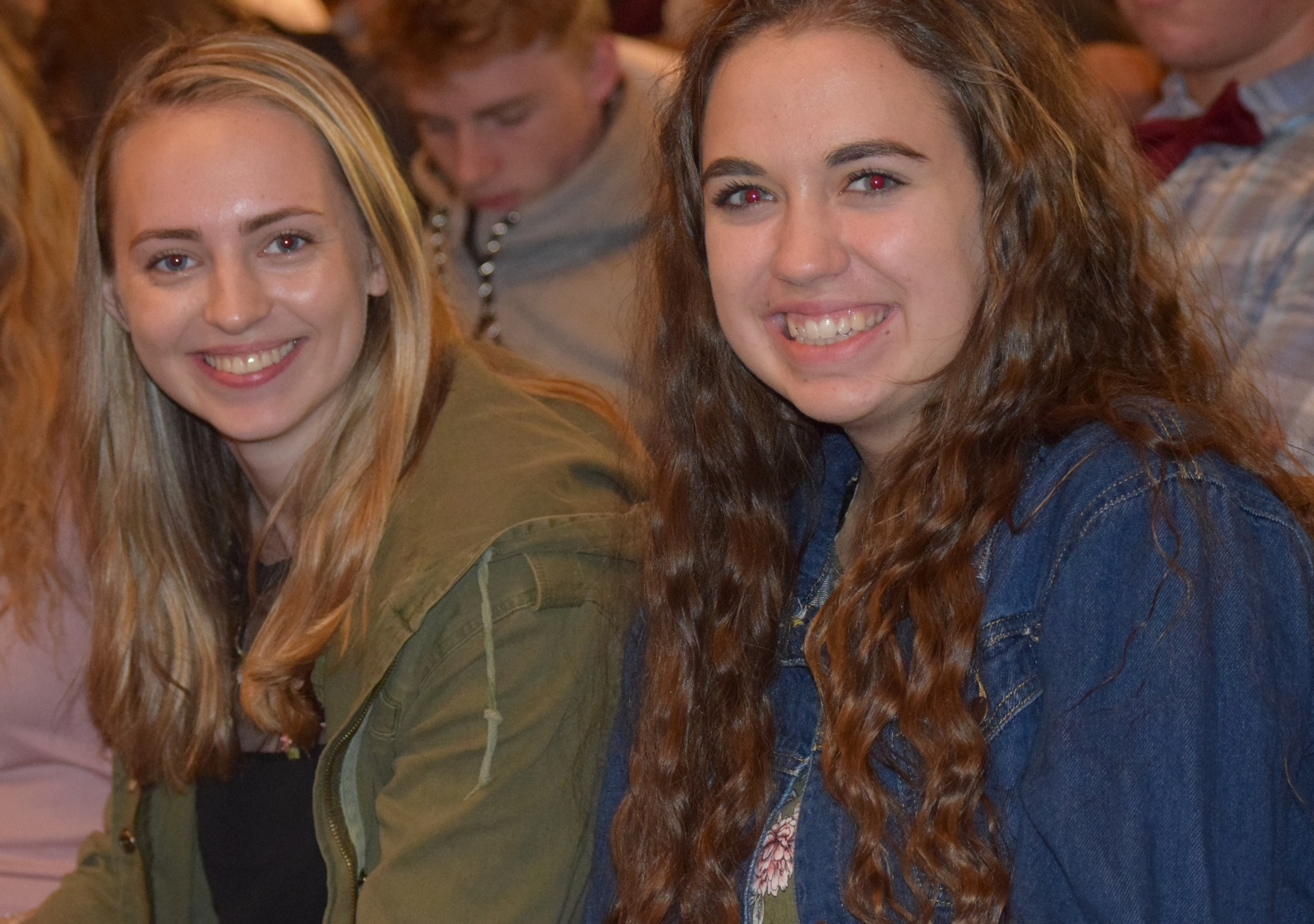 Two girls sitting in church pew.