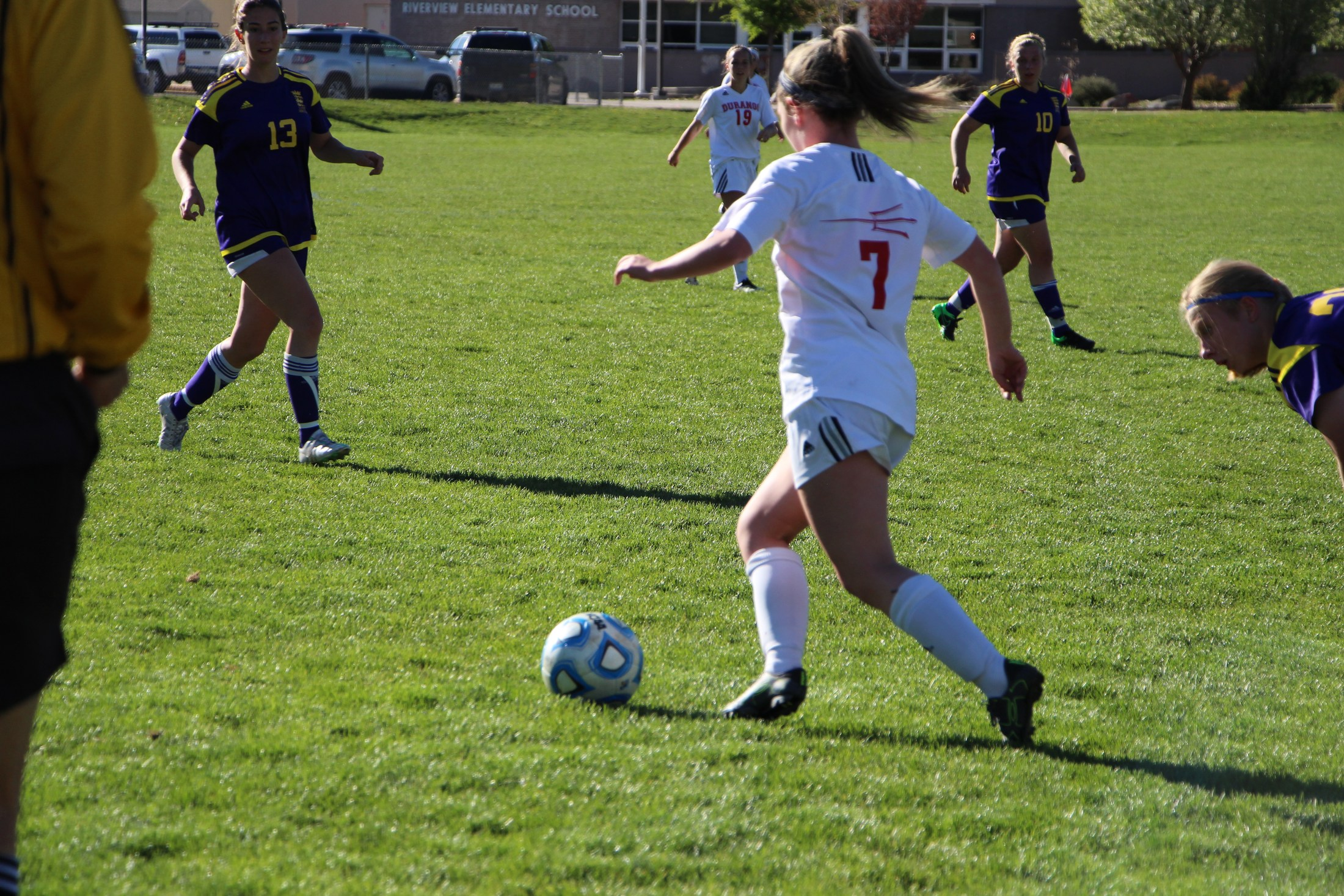 A DHS soccer striker kicks the ball up the field.