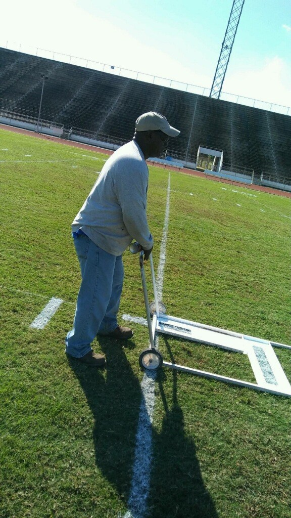 Groundsman working on football field.