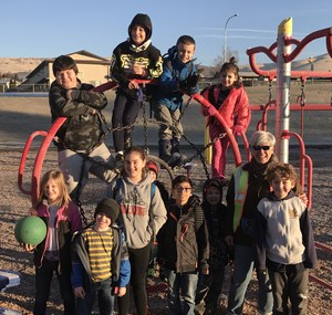 Cherie Trammell posing with students outside on the play structure equipment.