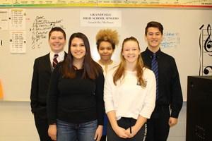 five high school students pose in choir room