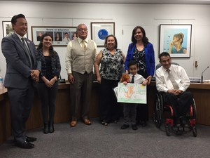 Elwin Elementary first-grader Josiah Fabian stands with his winning Red Ribbon Week poster with Baldwin Park Unified Superintendent Froilan N. Mendoza and members of the Board of Education on Nov. 8.