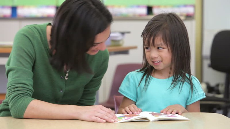 Teacher assisting student at desk