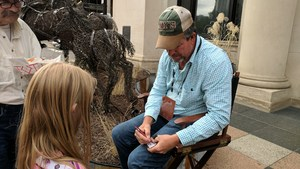 An elementary student gets an autograph from one of the artists at ArtPrize.
