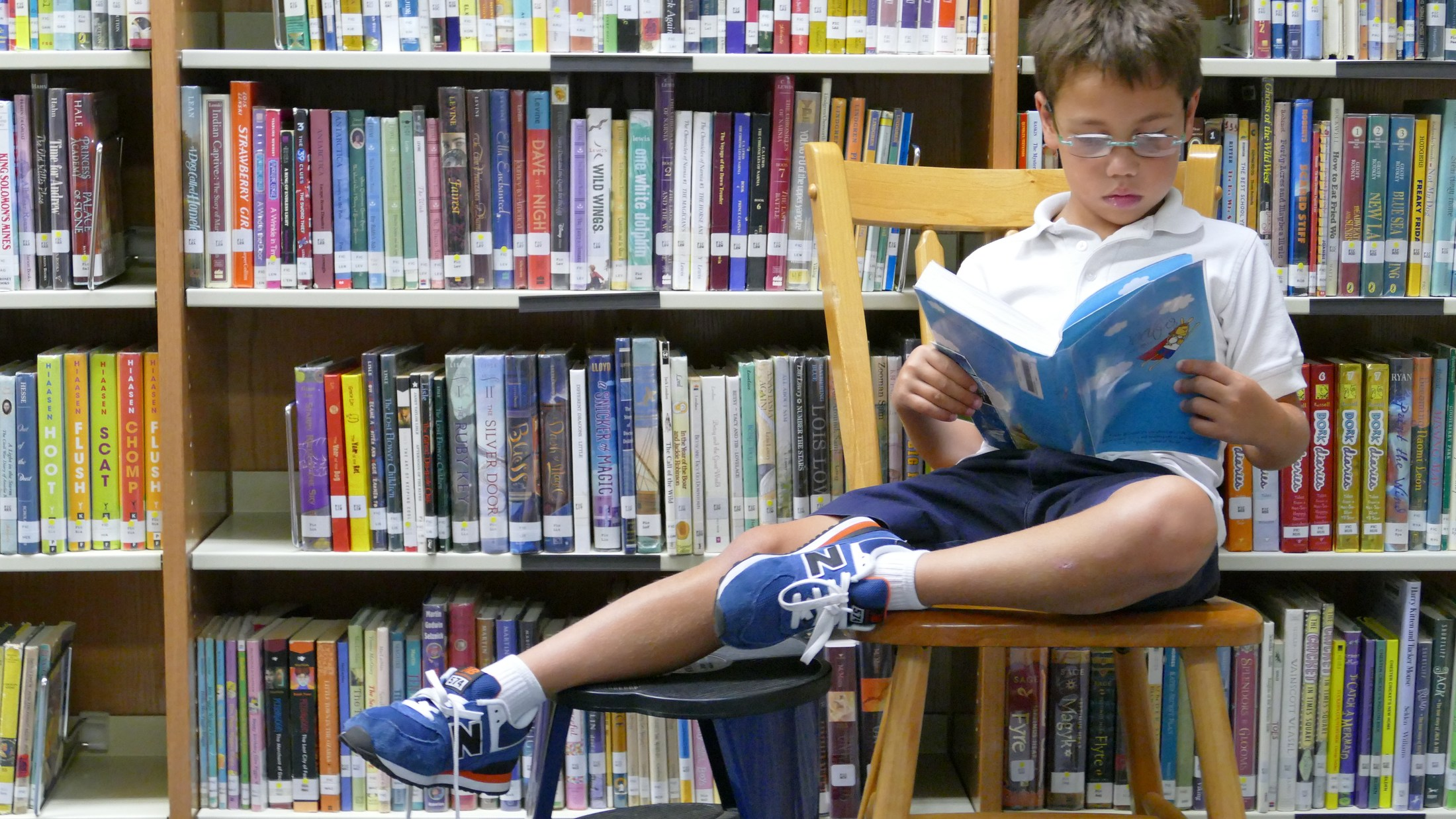 Boy student reading in library.
