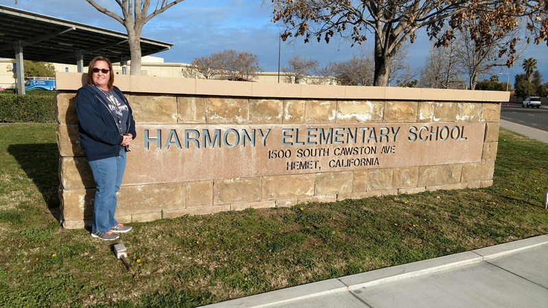 Renee Bush in front of a Harmony Elementary School sign.