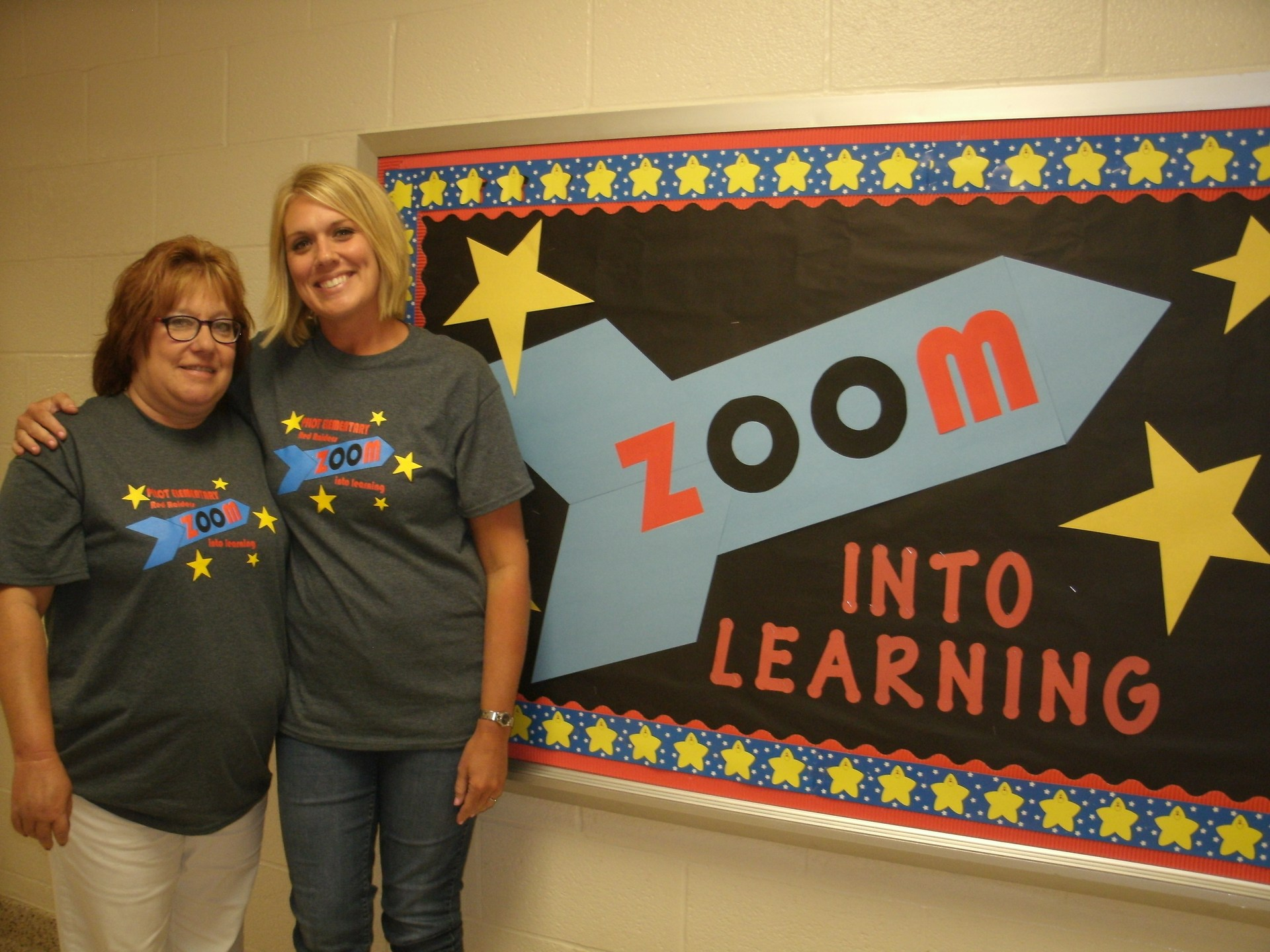 Two fourth grade teachers are standing in front of a bulletin board.