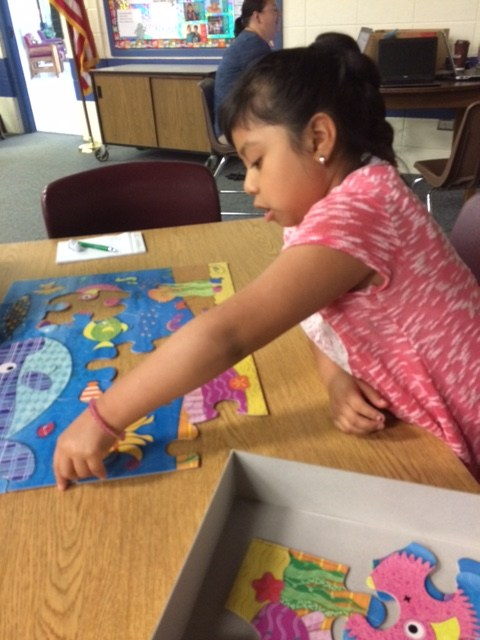 Eastfield Global Magnet School YMCA Afterschool Child playing with a puzzle