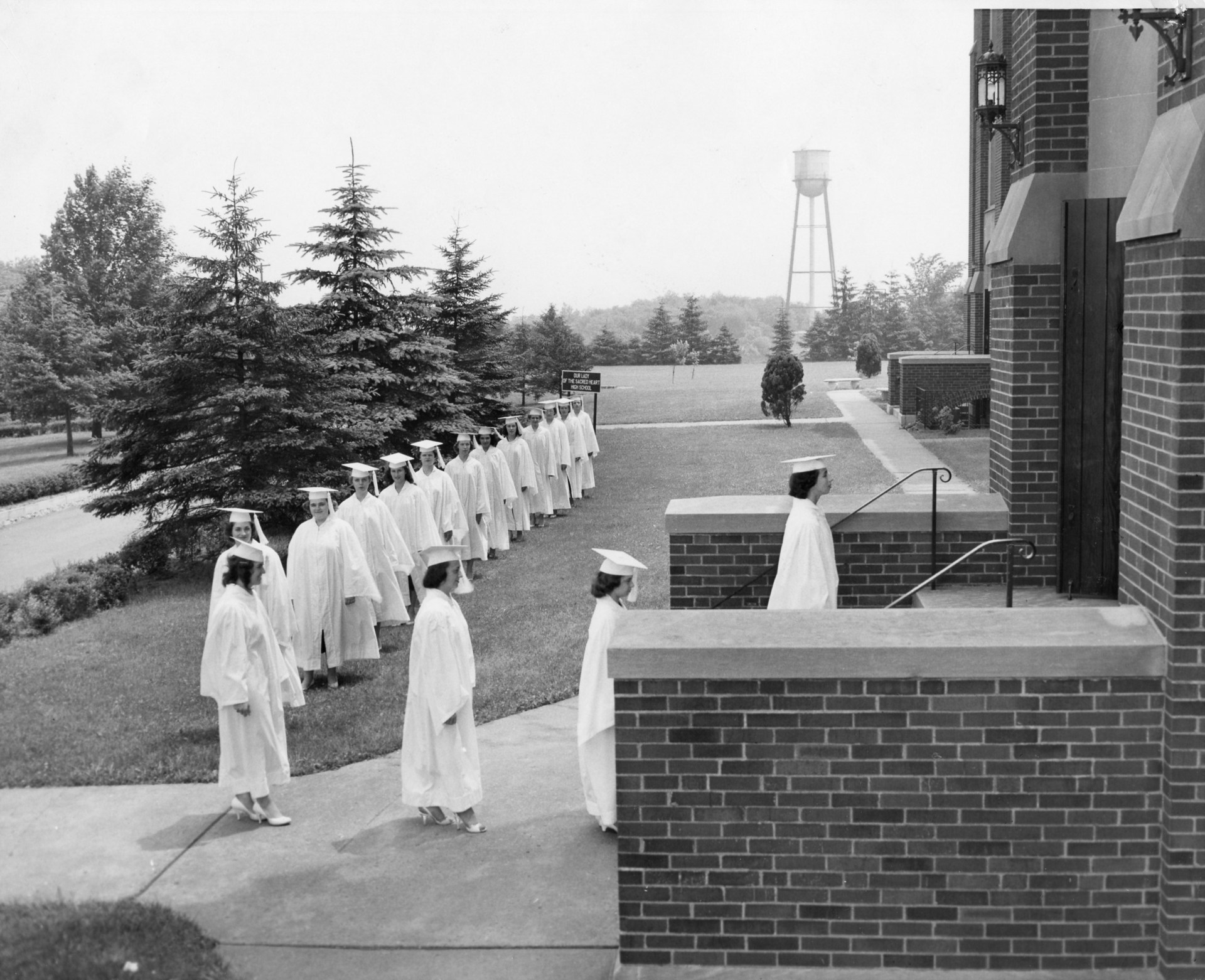 A line of graduates files into the OLSH school building in the 1950s.