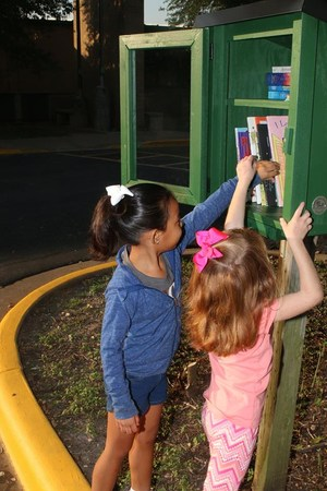 Kindergarteners are borrowing books from the Free Little Library.