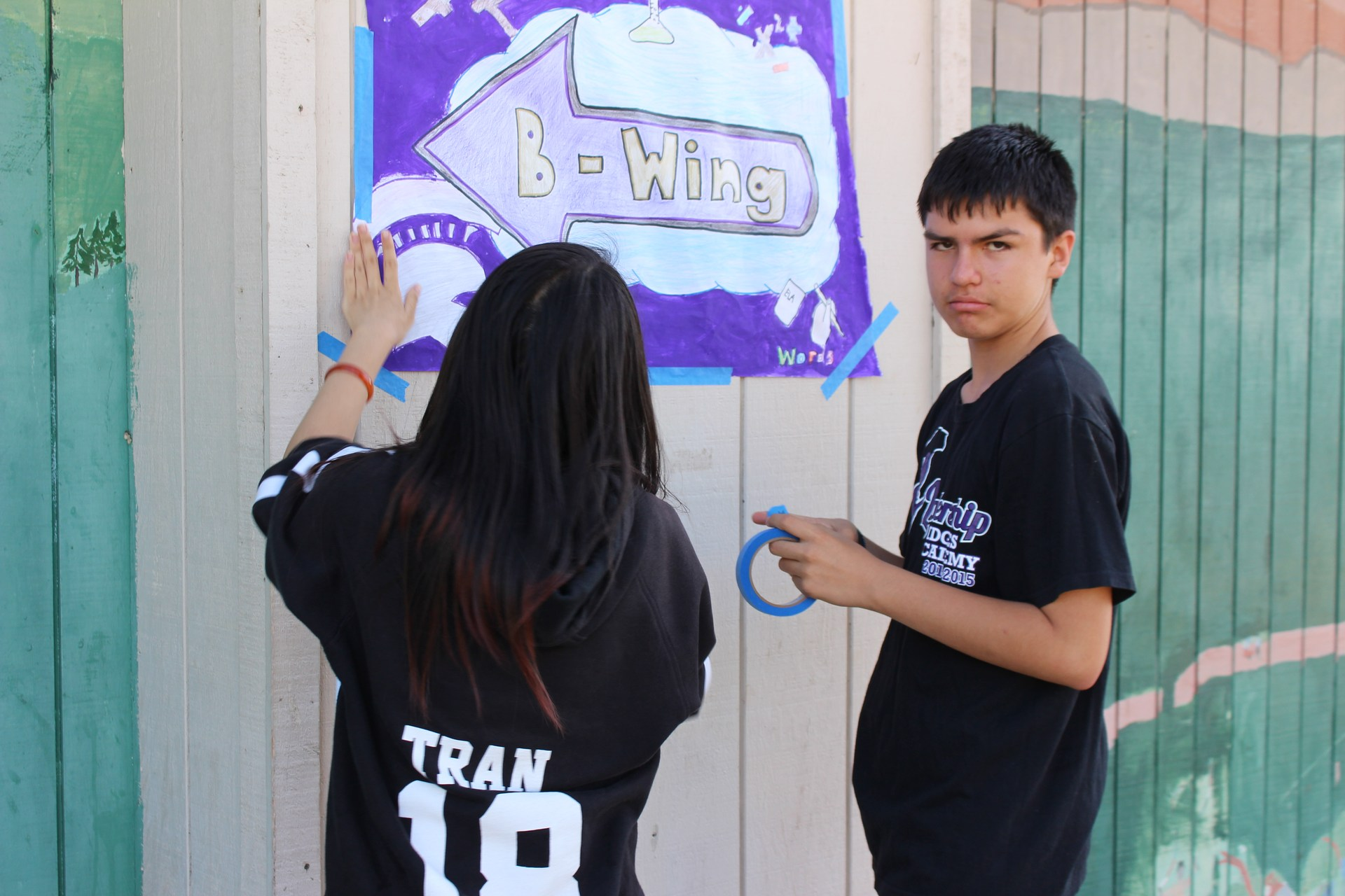 two students placing a poster on an outside wall