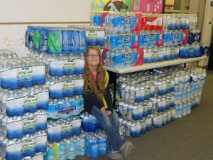 McFall first grader Scarlette Liesenfelder is surrounded by donations of water for Flint.