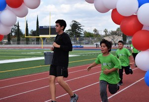 Students round the track on March 23 to cross the finish line and complete the last mile of a 26.2-mile marathon. Rod Dixon's Kids Marathon Run Club is an international program that teaches the benefits of regular exercise and nurtures a passion for running.
