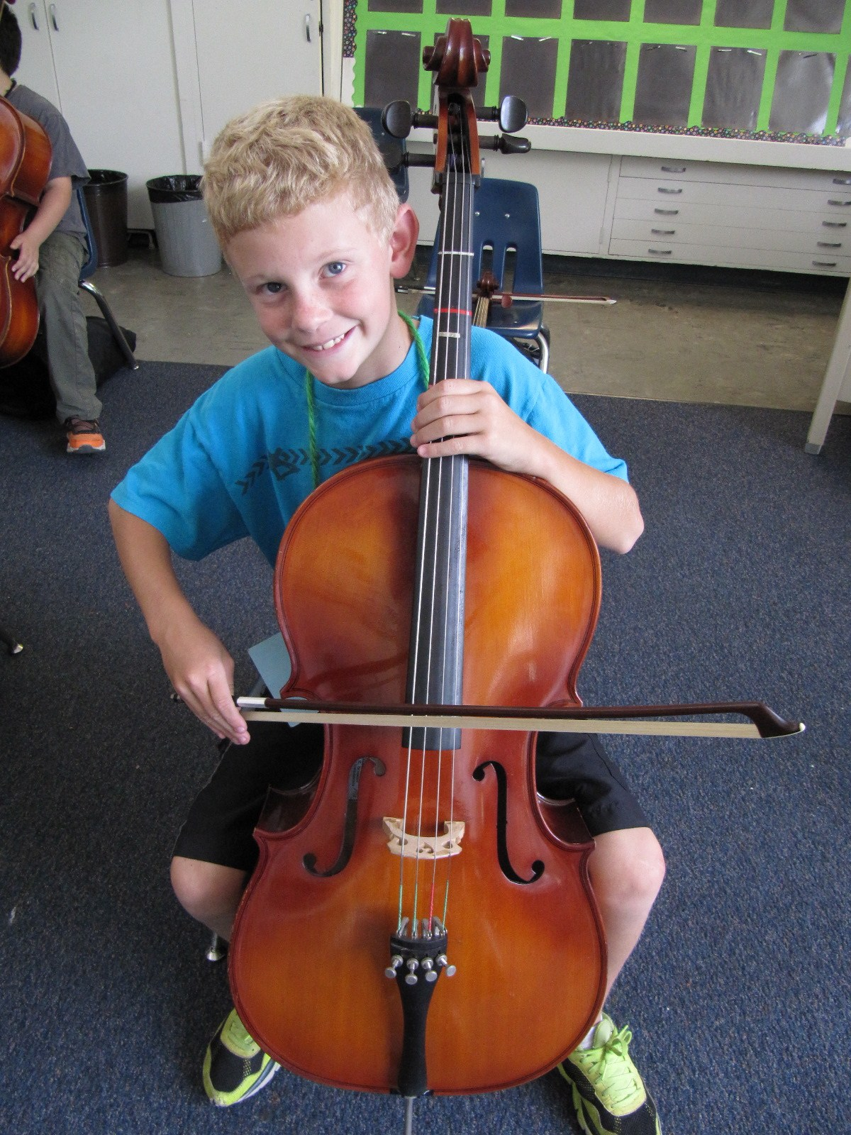 A boy playing a cello.