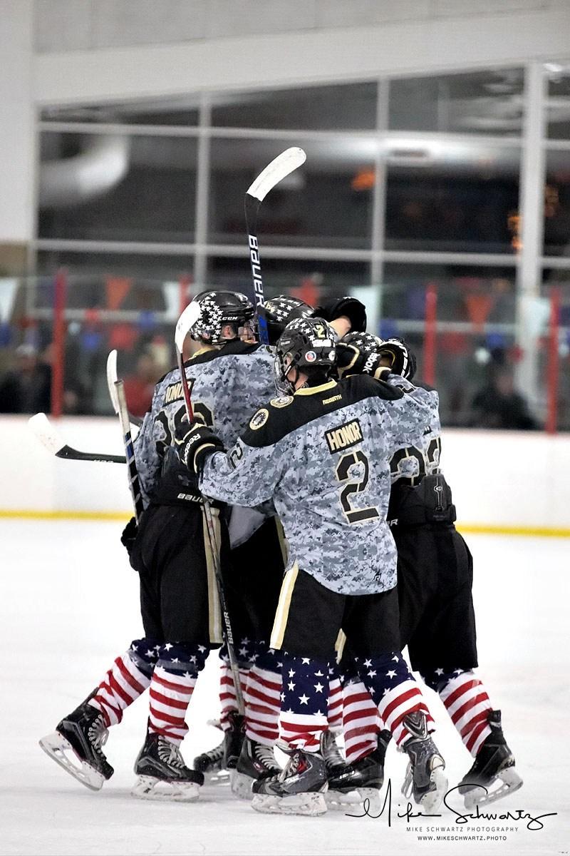 CHS ice hockey team celebrates on ice after a goal