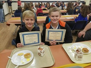 Two students showing their V.I.P. certificates.