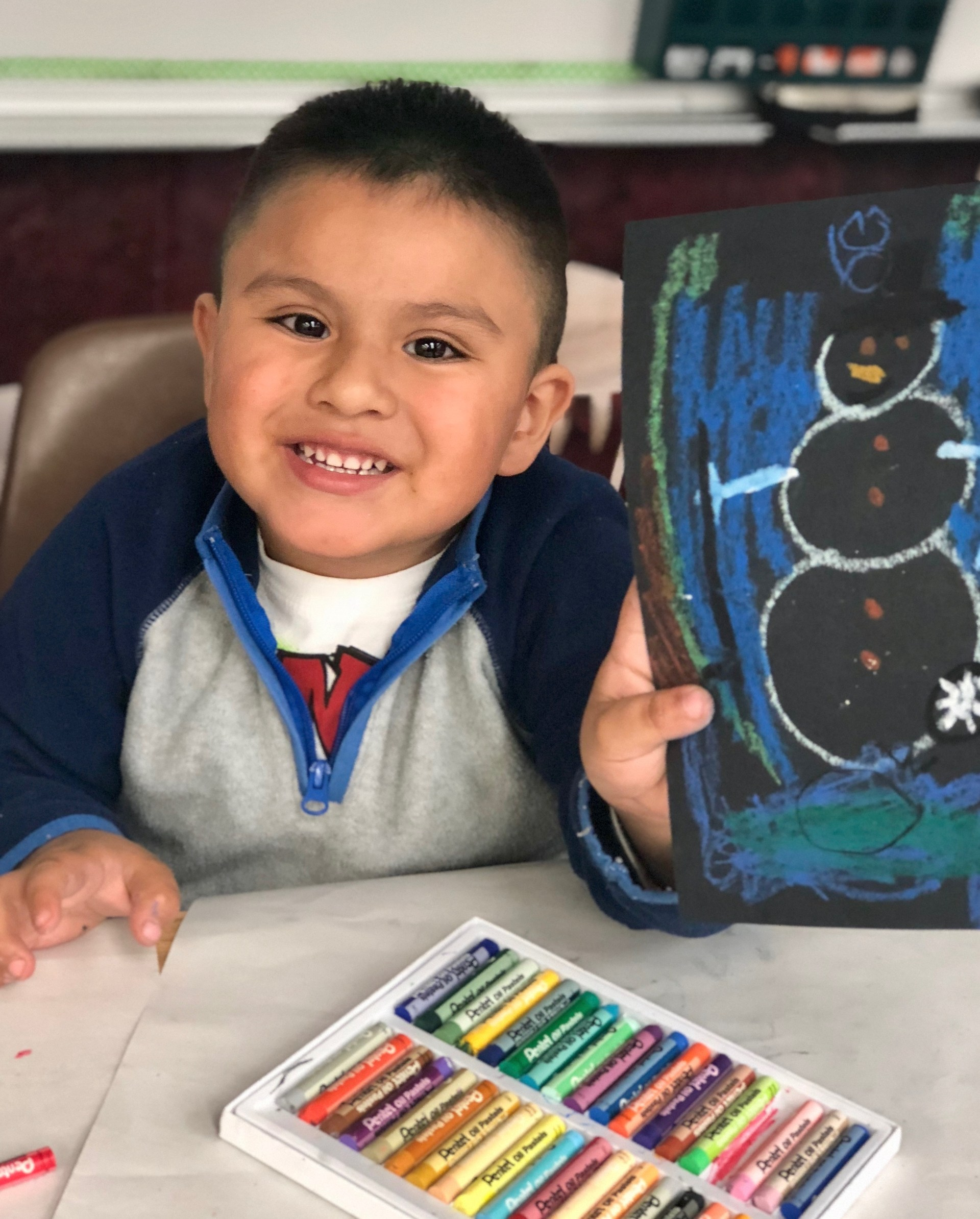 Boy showing his picture of a snowman.