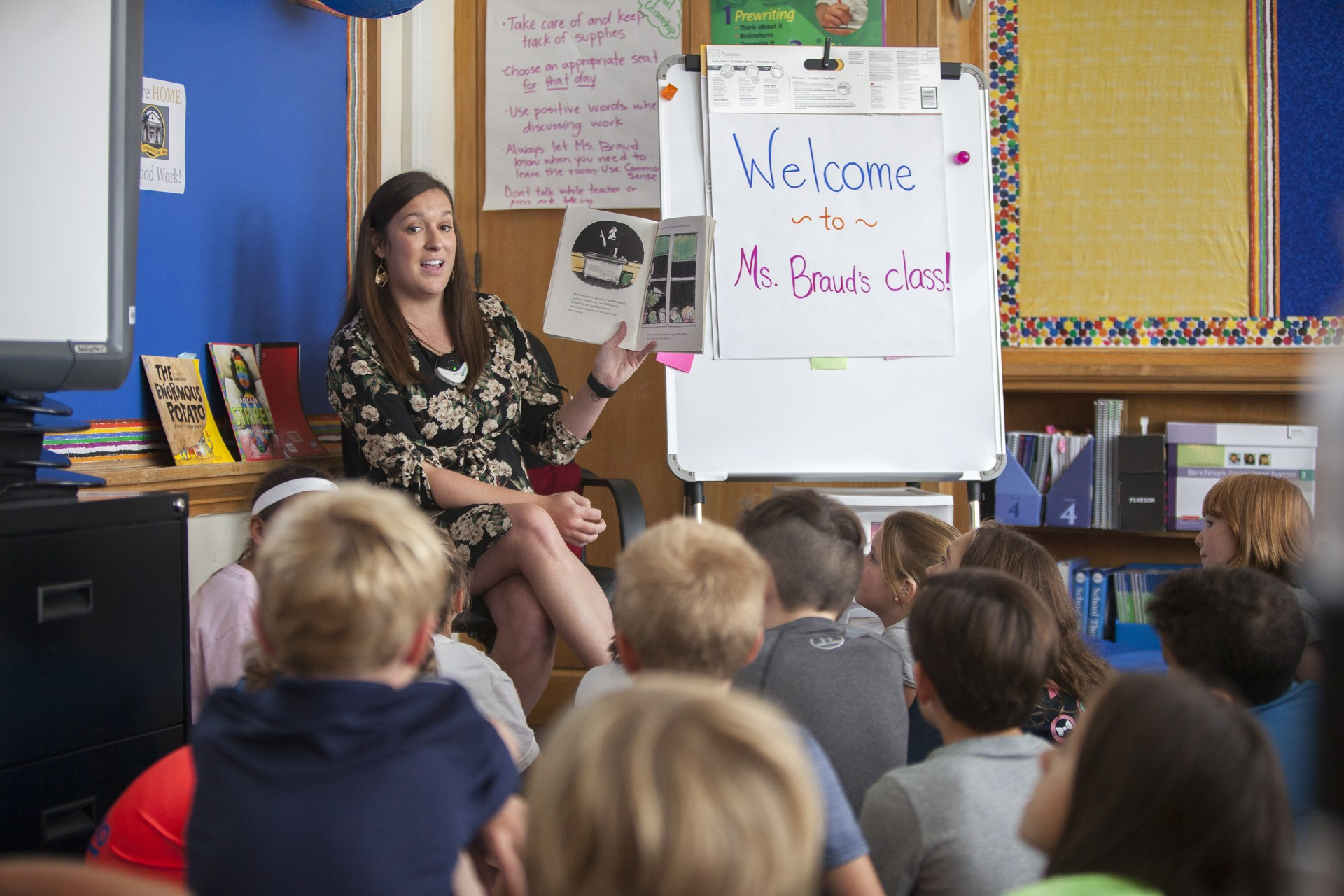 An elementary school teacher reads to her students in the classroom.